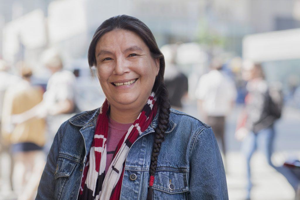 Indigenous woman stands near a city street
