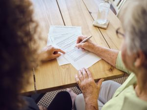 Senior Woman Signing Documents
