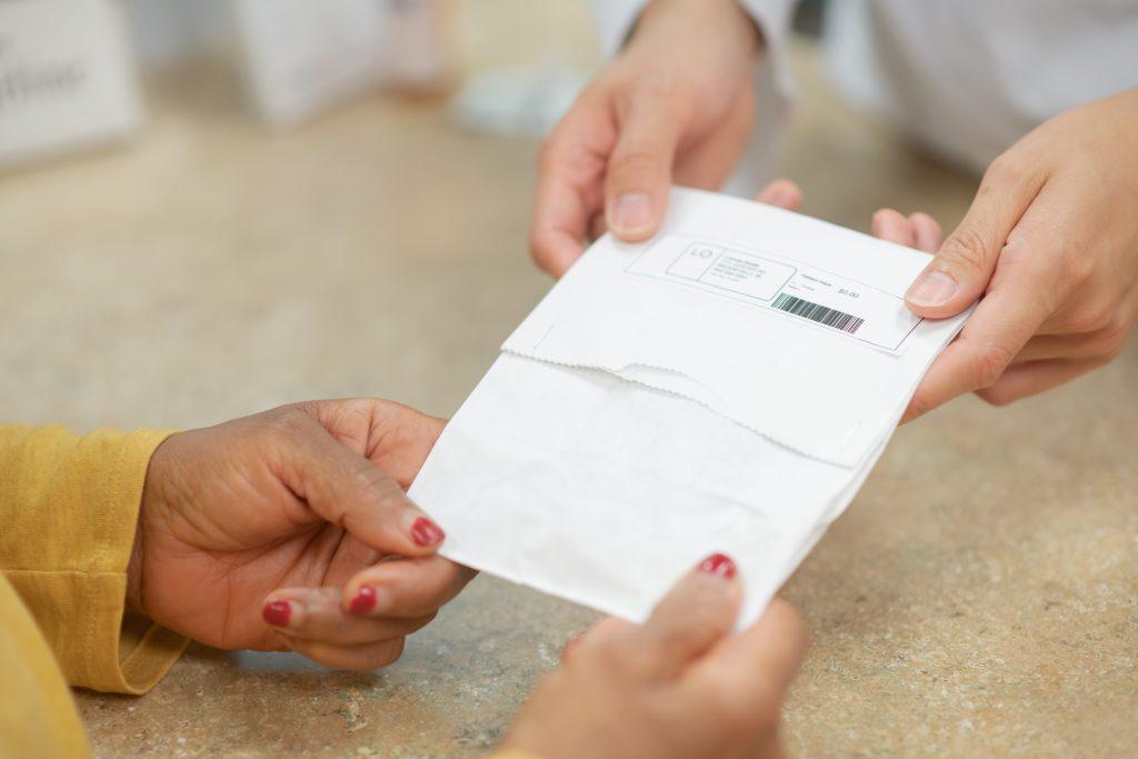 pharmacist handing customer prescriptions