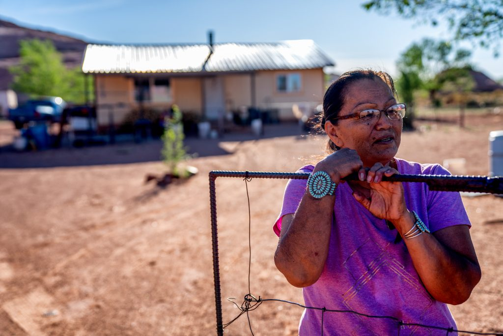 Native woman standing in front of home in desert